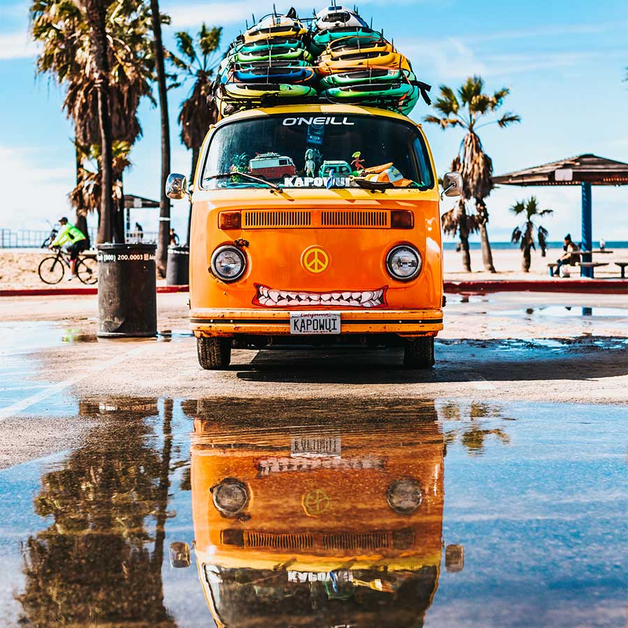 volkswagen campervan stacked with surfboards