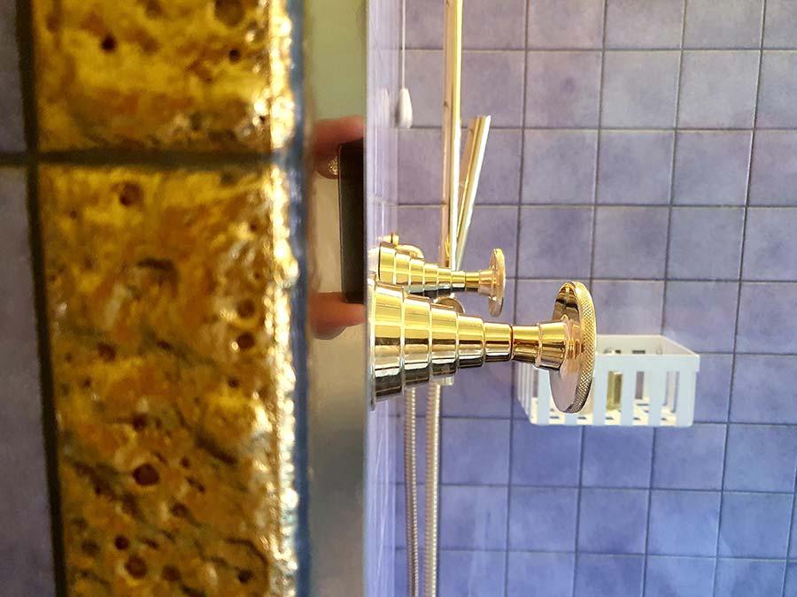 gold taps purple tiles bathroom