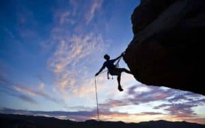 Figure 16.2 Mountain climber holding on by one hand over a vertical drop. Total concentration on immediate situation is demanded