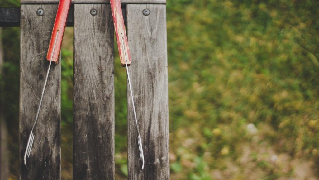 BBQ tongs hanging on fence post