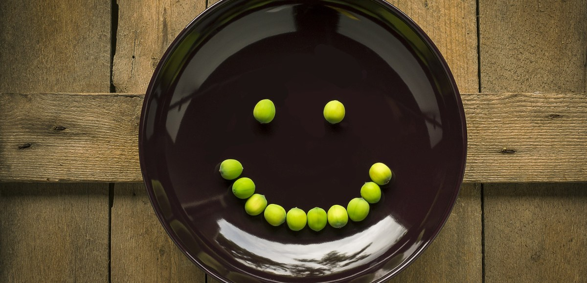 Plate with smiley face made out of peas on wood surface