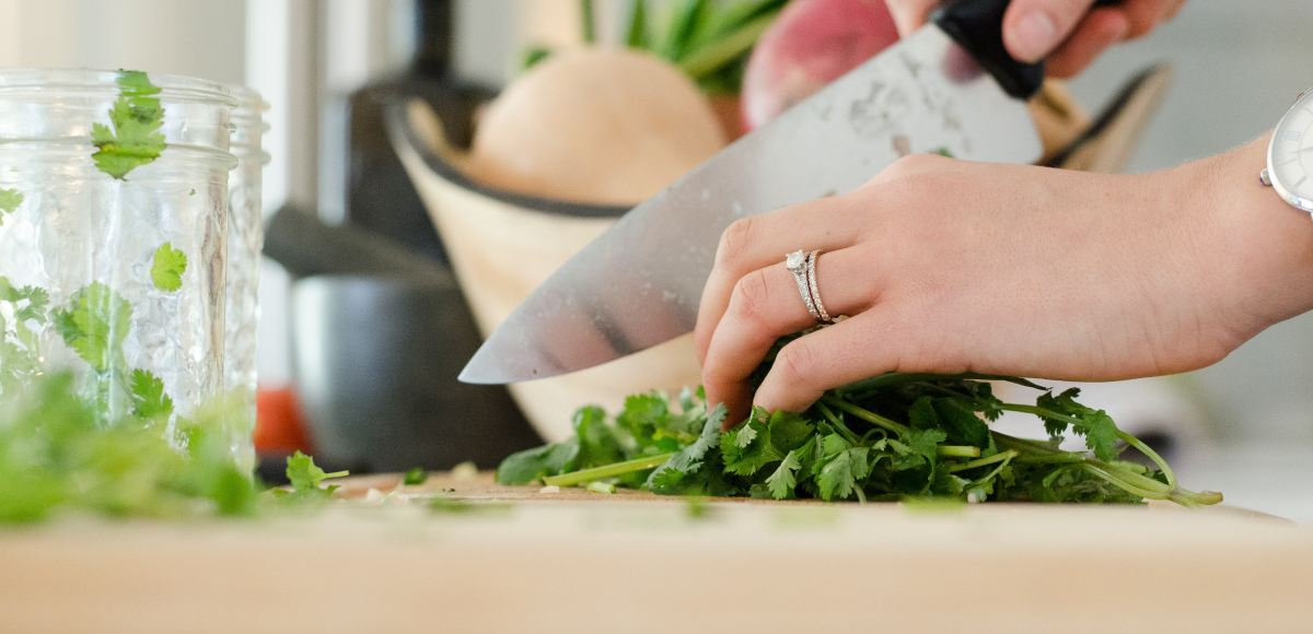 Woman chopping herbs on cutting board