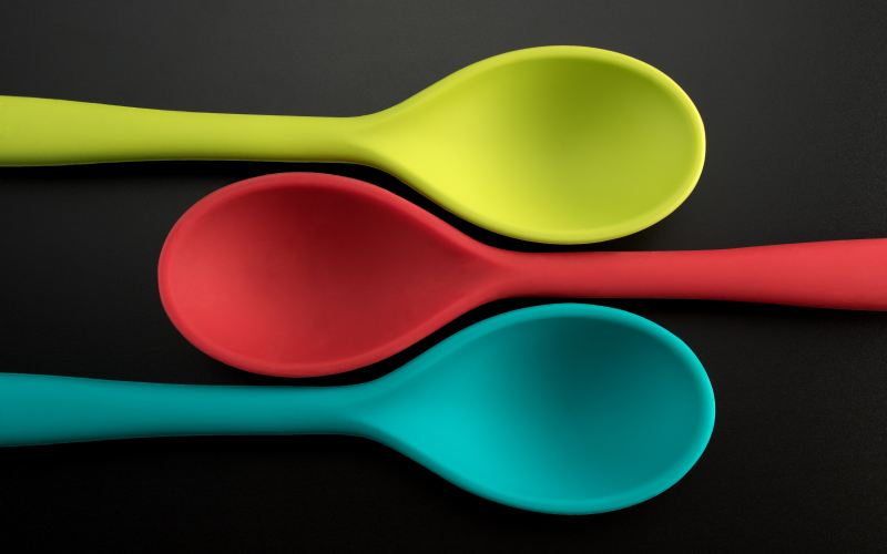 Colourful cooking spoons on black backdrop