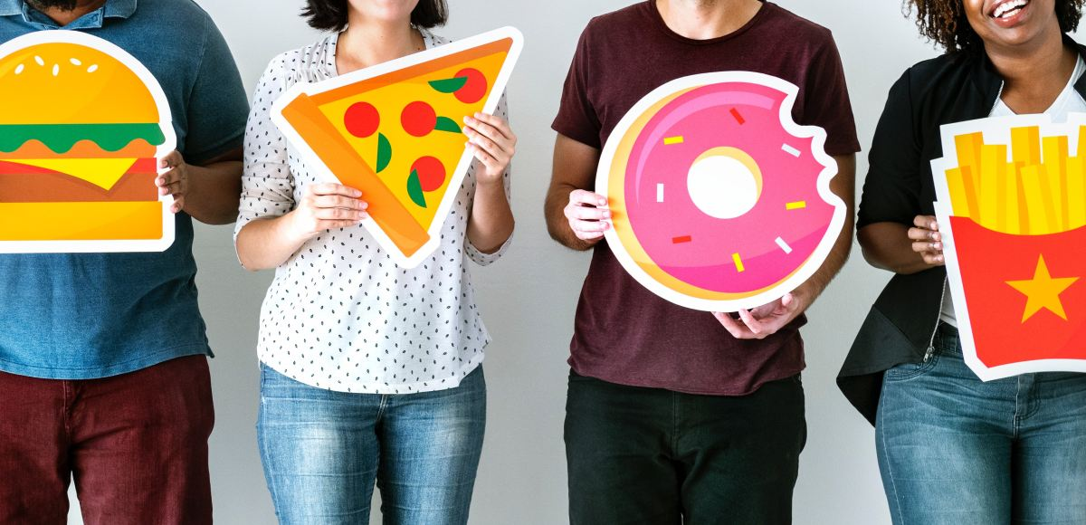 People holding cartoon images of junk foods. The best ways to banish your food cravings fast