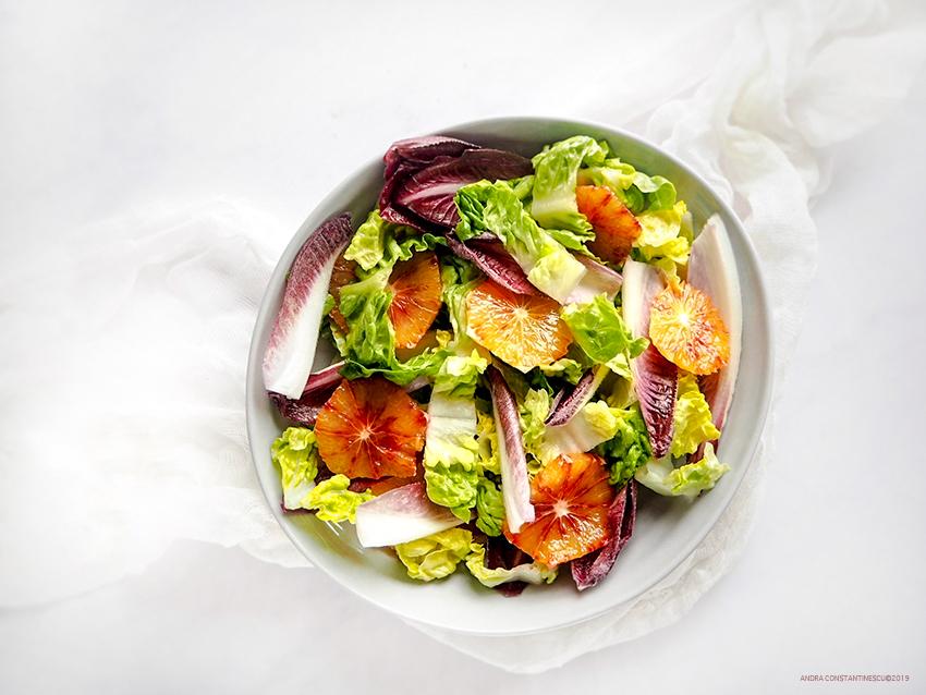 Un castron cu salata verde, andive si portocale rosii
