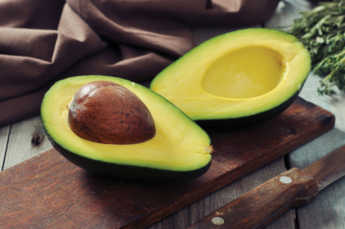 Fresh avocado on cutting board over wooden background