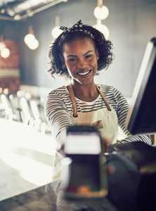 Smiling restaurant waitress holding an electronic card payment m