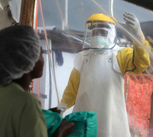 doctor and woman in ebola protective suits