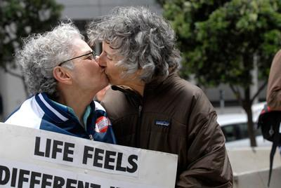 Shelly Bailes shares a kiss with Ellen Pontac, left, both of Oakland, in front of the Philip Burton federal building in San Francisco, Calif. on Wednesday, Aug. 4, 2010. The court ruled that Prop 8 is unconstitutional. (Dan Honda/Staff)