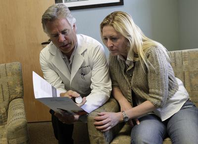 Dr. Andrew Cook goes over information on hormone supplements with patient Lisa Collins at his office in Los Gatos on Aug. 16, 2010. (Gary Reyes /Mercury News)