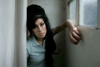 FILE - In this Feb. 16, 2007 file photo, British singer Amy Winehouse poses for photographs after being interviewed by The Associated Press at a studio in north London, Friday, Feb. 16, 2007. British police say singer Amy Winehouse has been found dead at her home in London on Saturday, July 23, 2011. The singer was 27 years old. (AP Photo/Matt Dunham, File)