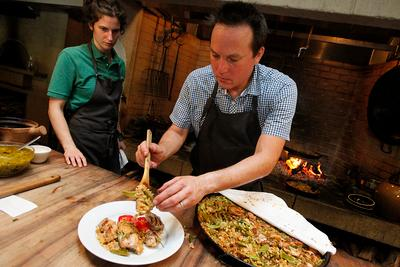 Camino sous chef Melissa Reitz, left, watches as chef Russell Moore plates a dish of paella on Monday, Aug. 20, 2012 in Oakland, Calif. Moore's paella dish consists of rabbit, shellbeans, romano beans, tomato, chilies, rice, crepinette and is cooked in the restaurant fireplace for about twenty minutes. (Aric Crabb/Staff)