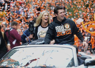 The San Francisco Giants' Buster Posey and his wife laugh as fans chant MVP during a parade to celebrate their 2012 World Series Championship down Market Street in downtown San Francisco, Calif. on Wednesday, Oct. 31, 2012. The Giants defeated the Detroit Tigers 4-0 to claim their second championship in the last 3 years. (Dan Honda/Staff)