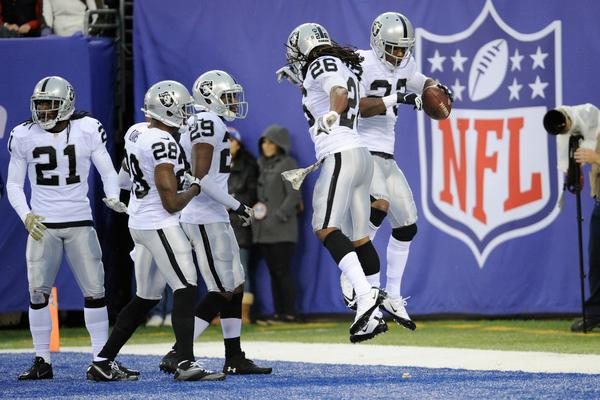 Oakland Raiders cornerback Tracy Porter, right, celebrates with teammates after running in a touchdown after intercepting a pass from New York Giants quarterback Eli Manning during the first half of an NFL football game on Sunday, Nov. 10, 2013, in East Rutherford, N.J. (AP Photo/Bill Kostroun)