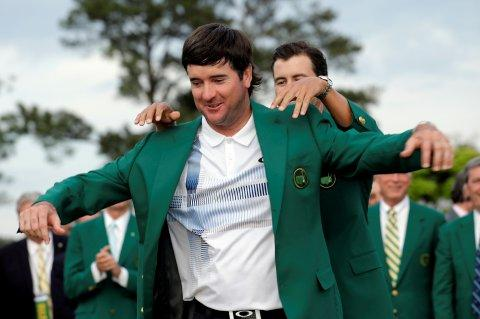 Defending Masters' champion Adam Scott, of Australia, helps Bubba Watson, left, with his green jacket after winning the Masters golf tournament Sunday, April 13, 2014, in Augusta, Ga. (AP Photo/David J. Phillip)
