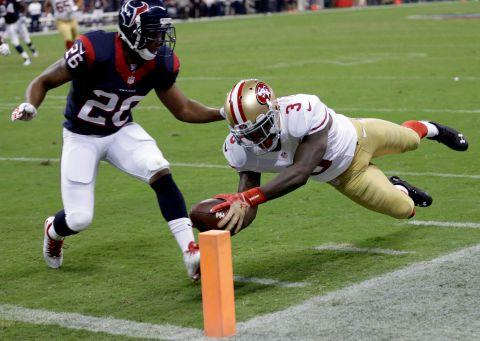San Francisco 49ers' Bruce Ellington (3) dives past Houston Texans' Brandon Harris (26) for a touchdown during the second quarter of an NFL football preseason game Thursday, Aug. 28, 2014, in Houston. (AP Photo/David J. Phillip)