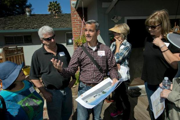 Land use consultant Erik Schoennauer, center, talks to homeowners about the impact that the Reserve, a 650-unit residential complex development being built in back of their homes, will have on them, in San Jose, Calif., on Saturday, April 4, 2015. (LiPo Ching/Bay Area News Group)
