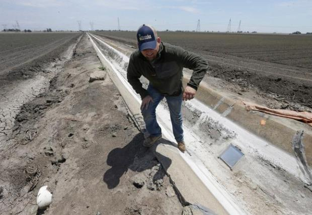 In this photo taken Monday, May 18, 2015, farmer Gino Celli climbs out of a irrigation canal that is covered in dried salt on a field he farms near Stockton, Calif. Celli, who farms 1,500 acres of land and manages another 7,000 acres, has senior water rights and draws his irrigation water from the Sacramento-San Joaquin River Delta. Farmers in the Sacramento-San Joaquin River Delta who have California's oldest water rights are proposing to voluntarily cut their use by 25 percent to avoid the possibility of even harsher restrictions by the state later this summer as the record drought continues.(AP Photo/Rich Pedroncelli)
