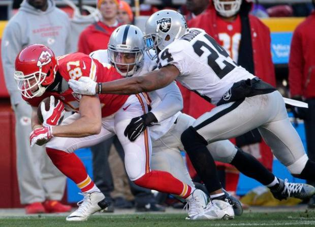 Kansas City Chiefs tight end Travis Kelce (87) is tackled by Oakland Raiders linebacker Malcolm Smith (53) and safety Charles Woodson (24), during the first half of an NFL football game in Kansas City, Mo., Sunday, Jan. 3, 2016. (AP Photo/Charlie Riedel)