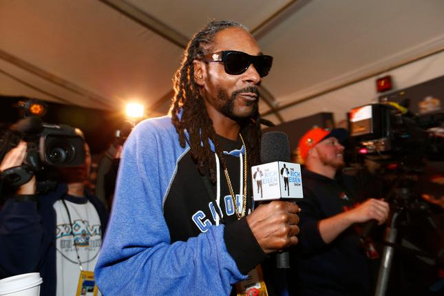 Rapper Snoop Dogg walks the room as he interviews Denver Bronco players during the Broncos daily press conference at the Santa Clara Marriott Hotel in Santa Clara Calif. on Thursday Feb. 4 2016. The Denver Broncos prepare to play the Carolina Panthers