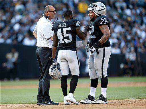 Oakland Raiders offensive line coach Mike Tice, left, talks with fullback Marcel Reece (45) and tackle Donald Penn (72) during the first half of an NFL preseason football game against the Arizona Cardinals in Oakland, Calif., Sunday, Aug. 30, 2015. (AP Photo/Tony Avelar)