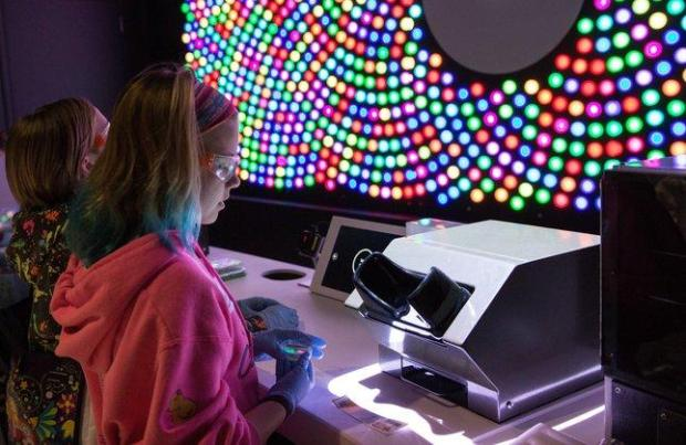 Kaitlyn Smiley, right, and Sarah Starkey, fifth-graders at Covington Schoolin Los Altos, explore a station where you can engineer multicoloredbacteria at BioDesign Studio, a new exhibit at the Tech Museum ofInnovation in downtown San Jose, on Friday, March 18, 2016. (JenniferBullock/Tech Museum of Innovation)