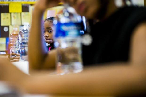 In this Jan. 25, 2016 file photo, third-grader Mayae Carradine listens to her teacher as she looks through a line of bottled water at Durant-Tuuri-Mott Elementary School, in Flint. In response to the city's lead-tainted water crisis, the school hands out bottles of water to students daily. Responding to the crisis in Flint, Michigan, school officials across the country are testing for lead in the water flowing from classroom sinks and cafeteria faucets to reassure anxious parents or take action if they are surprised by the results.