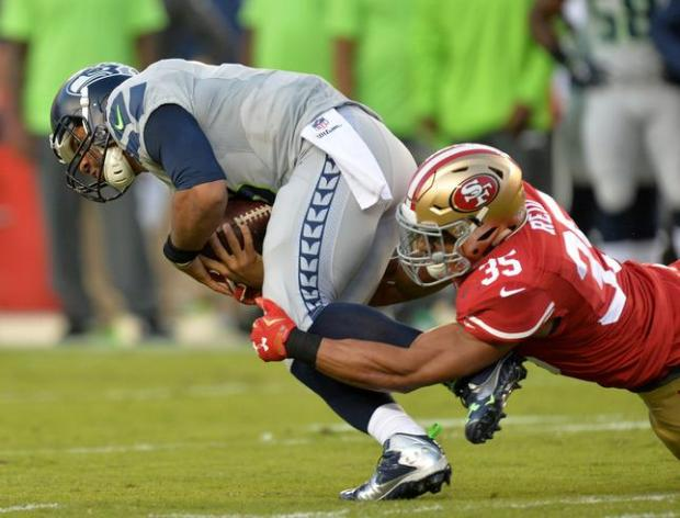 Seattle Seahawks quarterback Russell Wilson (3), left, gets tackled by San Francisco 49ers free safety Eric Reid (35) after running for a first down in the first quarter of their NFL game at Levi's Stadium in Santa Clara, Calif., on Thursday, Oct. 22, 2015. (Doug Duran/Bay Area News Group)