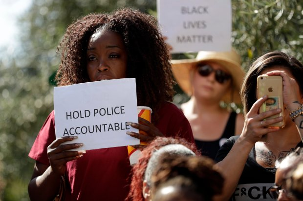 """People hold signs during a protest in front of the El Cajon Police Department Wednesday, Sept. 28, 2016, in El Cajon, Calif. A black man reportedly acting erratically at a strip mall in El Cajon was shot and killed Tuesday by police after pulling an object from his pocket, pointing it at officers and assuming a """"shooting stance,"""" authorities said. (AP Photo/Gregory Bull)"""