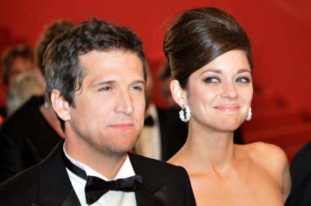 "French actress Marion Cotillard (R) looks at her partner director Guillaume Canet on May 20, 2013 as they leave after attending the screening of the film ""Blood Ties"" presented Out of Competition at the 66th edition of the Cannes Film Festival in Cannes. Cannes, one of the world's top film festivals, opened on May 15 and will climax on May 26 with awards selected by a jury headed this year by Hollywood legend Steven Spielberg. AFP PHOTO / ALBERTO PIZZOLI (Photo credit should read ALBERTO PIZZOLI/AFP/Getty Images)"