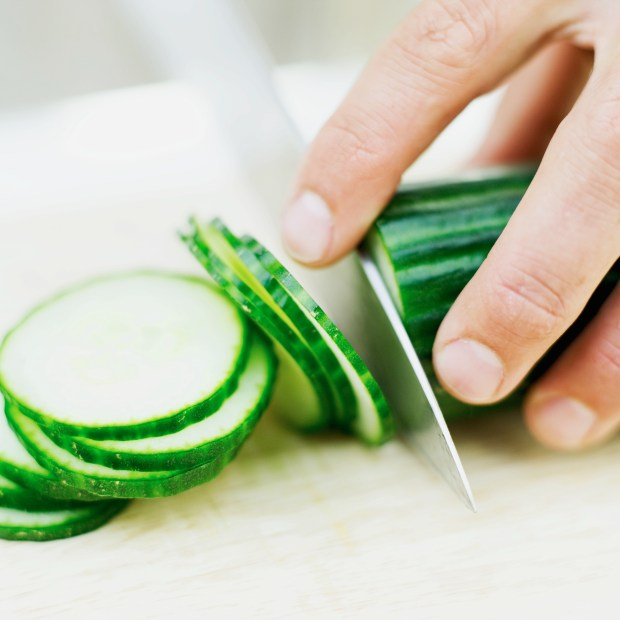 close-up of a person slicing cucumber (Thinkstock photo)