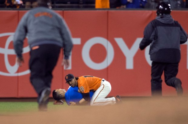 San Francisco Giants' Angel Pagan (16) holds down a man who ran onto the field during the fourth inning of the Giants' baseball game against the Los Angeles Dodgers, Friday, Sept. 30, 2016, in San Francisco. (AP Photo/D. Ross Cameron)