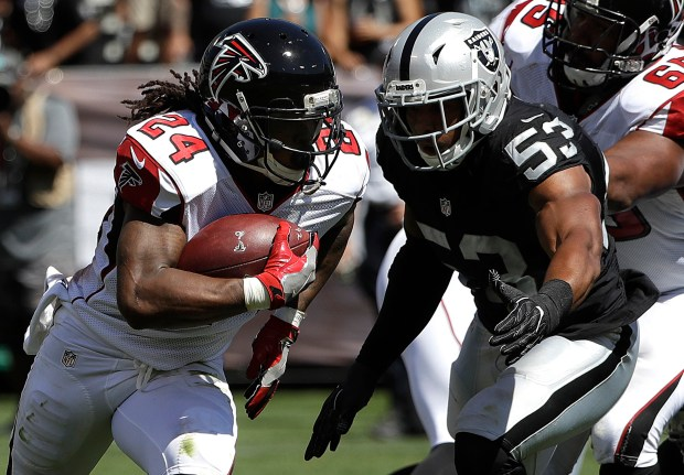 Atlanta Falcons running back Devonta Freeman (24) runs past Oakland Raiders linebacker Malcolm Smith (53) during the first half of an NFL football game in Oakland, Calif., Sunday, Sept. 18, 2016. (AP Photo/Marcio Jose Sanchez)