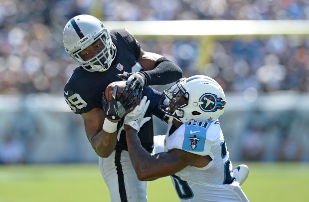 Oakland Raiders wide receiver Amari Cooper (89) tries to hold onto a pass as he is defended by Tennessee Titans cornerback Perrish Cox (20) in the first half of an NFL football game Sunday, Sept. 25, 2016, in Nashville, Tenn. (AP Photo/Mark Zaleski)
