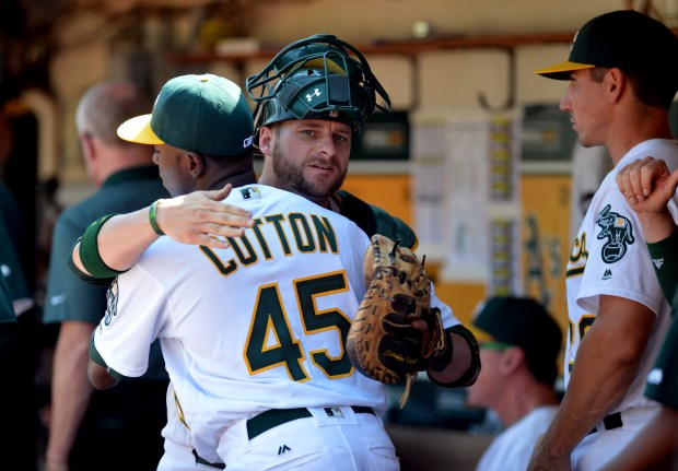 Oakland Athletics starting pitcher Jharel Cotton (45) receives a hug from catcher Stephen Vogt (21) in the dugout during a game against the Los Angeles Angels at the Oakland Coliseum in Oakland, Calif., on Wednesday, Sept. 7, 2016. In his major league debut, Cotton gave up two hits and one run in the Athletics' 4-1 win over the Angels. (Kristopher Skinner/Bay Area News Group)