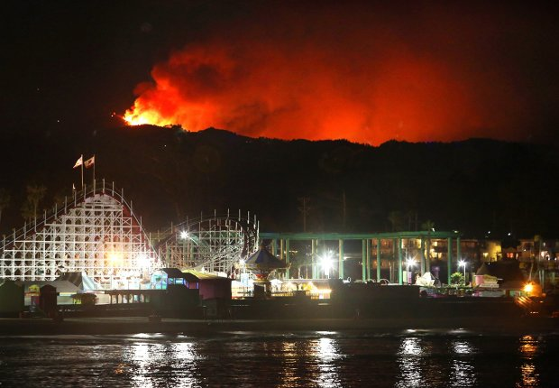The Loma Fire rages on the Santa Cruz mountains summit above the Santa Cruz Beach Boardwalk's Giant Dipper roller coaster. (Shmuel Thaler/Santa Cruz Sentinel)