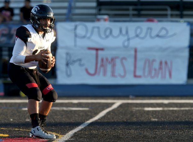James Logan quarterback Irvin Garnica (17) warms up in front of a banner calling for prayers for the team placed by Clayton Valley Charter before their football game in Concord, Calif., on Friday, Sept. 16, 2016. Students senior and linebacker Izaiah Mease and junior Joe Ioramo were both killed in a car crash on Interstate 880 in Hayward. (Anda Chu/Bay Area News Group)