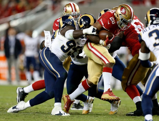 San Francisco 49ers' Carlos Hyde (28) runs with the ball against Los Angeles Rams' William Hayes (95) in the fourth quarter of their NFL game at Levi's Stadium in Santa Clara, Calif., on Monday, Sept. 12, 2016. (Nhat V. Meyer/Bay Area News Group)