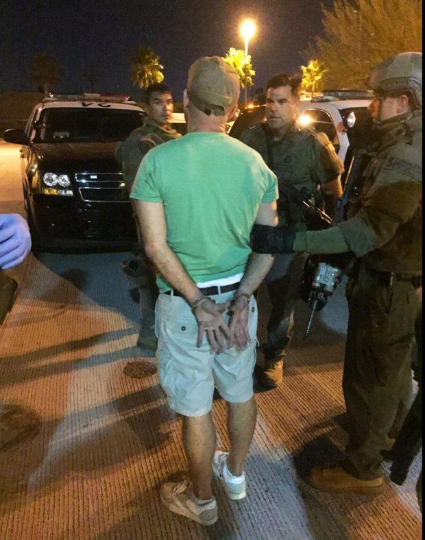 This photo provided by the Los Angeles County Sheriff's Department shows a suspect taken into custody after an hours-long standoff after an armed man barricaded himself aboard an Amtrak train at the Metrolink station in the Chatsworth area of Los Angeles in the early morning hours of Saturday, Sept. 17, 2016. Nearly 200 passengers and crew on the train bound for San Diego were evacuated Friday night after several reported seeing a man with a weapon. (AP Photo/Los Angeles County Sheriff's Department via AP)