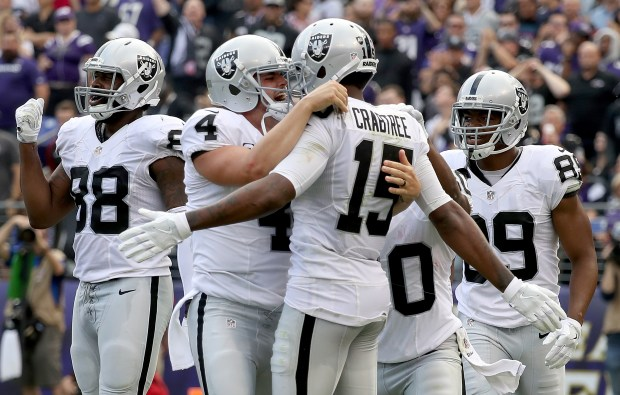 Derek Carr #4 and Michael Crabtree #15 of the Oakland Raiders celebrate after scoring a touchdown in the fourth quarter against the Baltimore Ravens at M&T Bank Stadium on October 2, 2016 in Baltimore, Maryland. (Photo by Rob Carr/Getty Images)