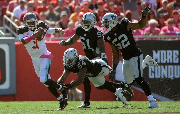 Tampa Bay Buccaneers quarterback Jameis Winston (3) eludes Oakland Raiders outside linebacker Perry Riley (54), outside linebacker Bruce Irvin (51) and defensive end Khalil Mack (52) during the first quarter of an NFL football game Sunday, Oct. 30, 2016, in Tampa, Fla. (AP Photo/Phelan Ebenhack)