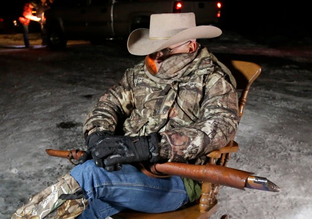 FILE - In this Jan. 5, 2016, file photo, Arizona rancher LaVoy Finicum, holds a rifle as he guards the Malheur National Wildlife Refuge near Burns, Ore. The stunning acquittal of seven people who occupied a federal bird refuge in Oregon as part of a Western land dispute was a rejection of the prosecution's conspiracy case, not an endorsement of the armed protest, a juror said Friday, Oct. 28, 2016. (AP Photo/Rick Bowmer, File)