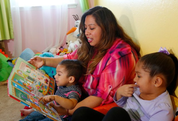 Jetzabel Gonzalez reads to her children, one-year-old, Matias Palma, and Frida Palma, 3, and at their home in San Jose, Calif., on Wednesday, Oct. 26, 2016. Gonzales participates in the NuParent Program at Grail Family Services which helps Spanish-speaking immigrants to give their kids a strong start to a lifetime of learning. (Gary Reyes/Bay Area News Group)