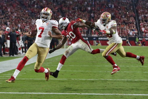 San Francisco 49ers quarterback Colin Kaepernick (7) runs for a touchdown as teammate Carlos Hyde, right, blocks Arizona Cardinals outside linebacker Deone Bucannon (20) during the second half of an NFL football game, Sunday, Nov. 13, 2016, in Glendale, Ariz. (AP Photo/Rick Scuteri)