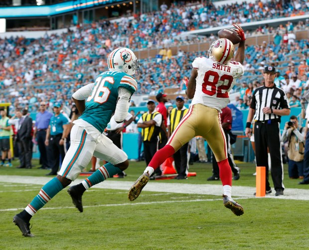 San Francisco 49ers wide receiver Torrey Smith (82) grabs a pass for a touchdown as Miami Dolphins cornerback Tony Lippett (36) is late with the tackle, during the second half of an NFL football game, Sunday, Nov. 27, 2016, in Miami Gardens, Fla. (AP Photo/Wilfredo Lee)