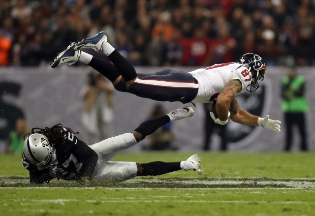 C.J. Fiedorowicz #87 of the Houston Texans is tackled by Reggie Nelson #27 of the Oakland Raiders in their game at Estadio Azteca on November 21, 2016 in Mexico City, Mexico. (Photo by Buda Mendes/Getty Images)