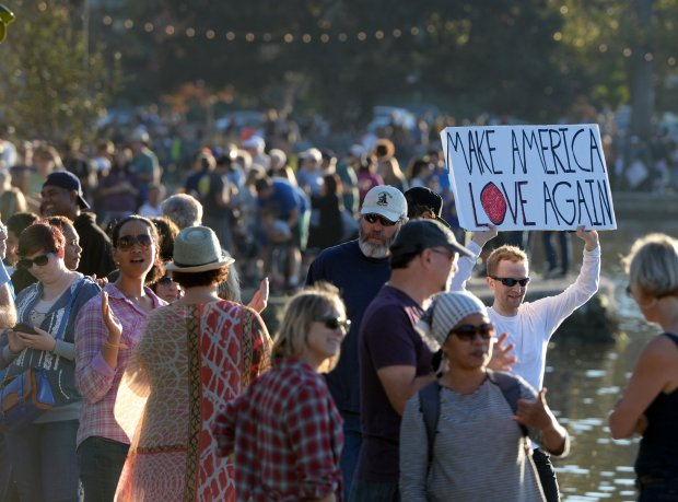 A jogger makes his way around the 3.4 miles of Lake Merritt as people hold hands, flash the peace sign and stand up against racism, sexism, homophobia and Islamophobia  in a peaceful way in Oakland, Calif., on Sunday, Nov. 13, 2016. (Susan Tripp Pollard/Bay Area News Group)