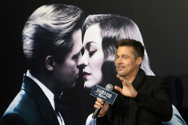 Actor Brad Pitt gestures to his fans as he attends a premiere of director Robert Zemeckis' new film 'Allied' in Shanghai, China, Monday, Nov. 14, 2016. Brad Pitt made his first promotional appearance for a movie in China since reportedly being banned over a film about Tibet almost 20 years ago. (Color China Photo via AP)