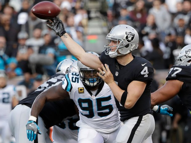 Oakland Raiders quarterback Derek Carr (4) passes against the Carolina Panthers during the second half of an NFL football game in Oakland, Calif., Sunday, Nov. 27, 2016. (AP Photo/Marcio Jose Sanchez)