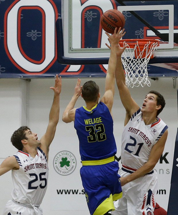 San Jose State's Ryan Welage (32) shoots between Saint Mary's Joe Rahon, left, and Evan Fitzner (21) during the first half of an NCAA college basketball game Tuesday, Nov. 22, 2016, in Moraga, Calif. (AP Photo/Ben Margot)